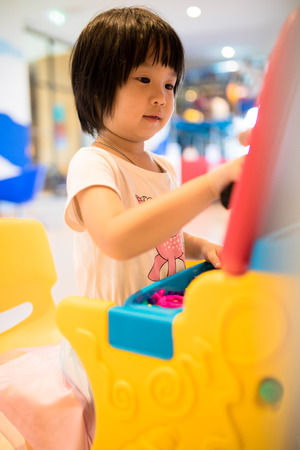 Asian kid focusing on her game in playroom Stock Photo