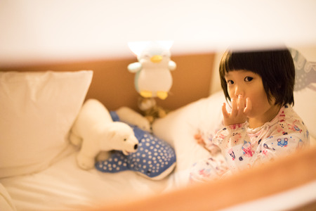 Asian kid sucking thumb and looking ponder in bed with dolls