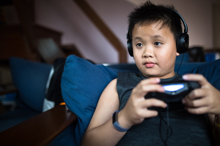 asian boy wearing headphone hold game console and look at the game monitor Stock Photo