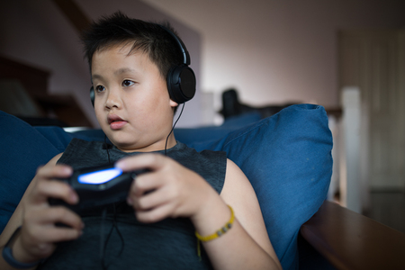 Asian boy wearing headphone hold game console and look at the game monitor in living room Stock Photo