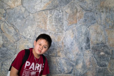 asian boy express silly face with brick wall background