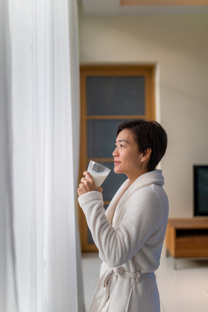 Asian woman drinking a glass of milk in living room and looking outside window with smile face Reklamní fotografie