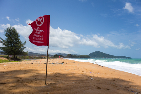 Red flag warning at polluted beach with trash