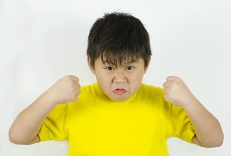 provoked: an angry child showing his temper and fists Stock Photo