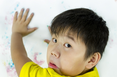 a child being caught while painting on the wall Stock Photo