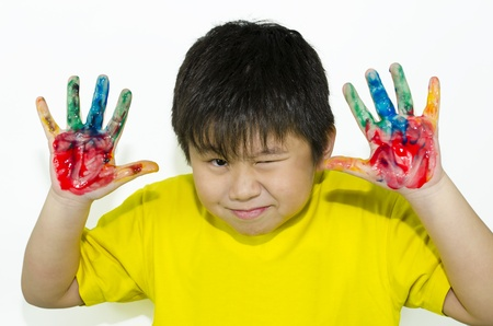 child with a funny expression and painting with hand photo