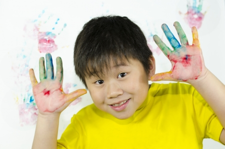 a child paints with his hand on a white wall photo