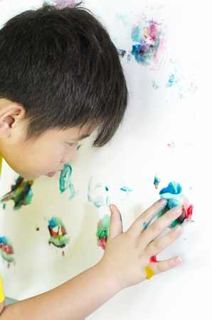 child painting with his handson the wall