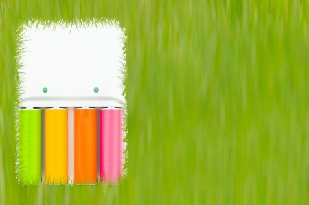 colorful rechargable batteries on a white charger against green grass backgrounds