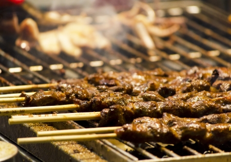 a local cooking meat skewers over charcoal Stock Photo