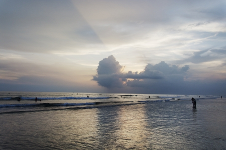 Rays of light on a setting sun against the famous Kuta beach of Bali