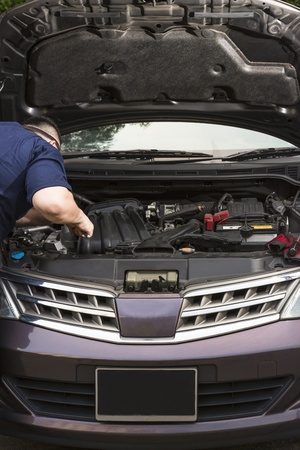 Frontal shot of a car mechanic fixing a car