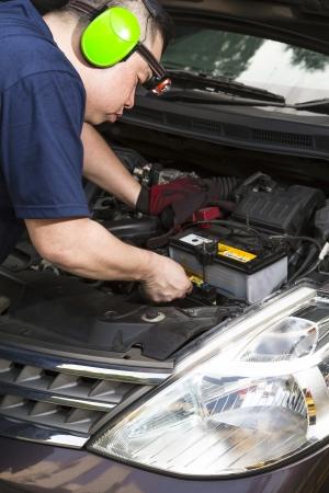 A car mechanic inspecting the car battery   Stock Photo