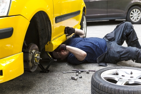 screw key: A mechanic underneath a car checking the car condition Stock Photo