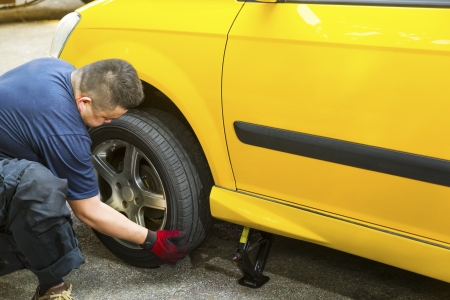 An Asian mechanic changing a car tire.