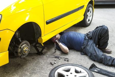 A mechanic underneath a yellow car doing maintain job.