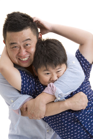 Asian Father and son playing bear hug on isolated white backrgound