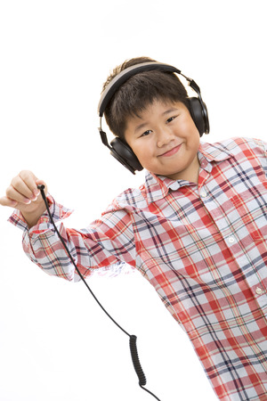 A smiling boy unplug his headphone on isolated background. photo