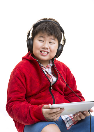 Vertical shot of a young Asian boy in red listening to music with a headphone isolated on white.