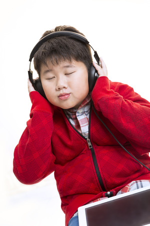 Vertical shot of a young Asian boy in red enjoying his moment  listening to music with a headphone isolated on white. Stock Photo