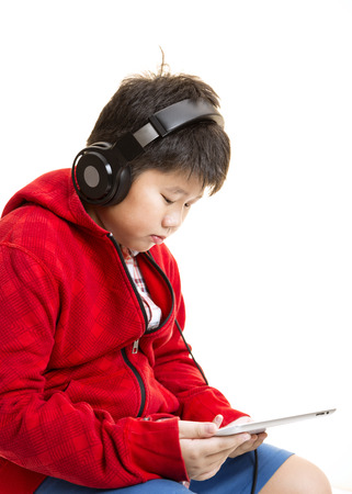 Side view vertical shot of a young Asian boy in red listening to music with a headphone isolated on white.