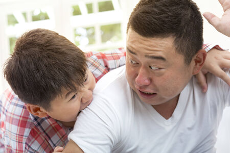 Asian son biting father shoulder while playing on isolated white backrgound