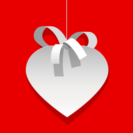 white heart: A white heart cut out of paper. with a Ribbon on a red.