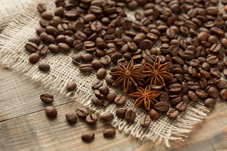 burlap sack: coffee beans, and star anise on wooden table Stock Photo