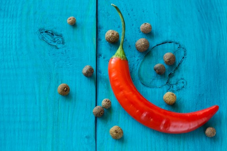 Red chili peppers and spicy pepper, on a wooden blue background