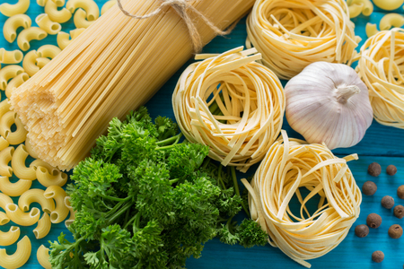 spaghetti and tagliatelle with ingredients for cooking pasta. Curly parsley, garlic on a blue background. top view. Stock Photo