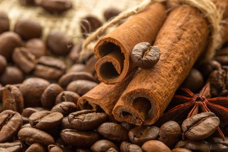 coffee beans, cinnamon sticks and cinnamon on burlap background. Stock Photo