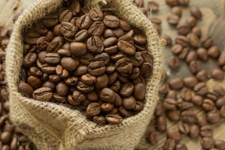coffee beans in a burlap bag on a wooden background Stock Photo