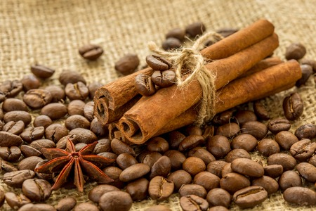 coffee beans, cinnamon sticks, and star anise on burlap background. Stock Photo