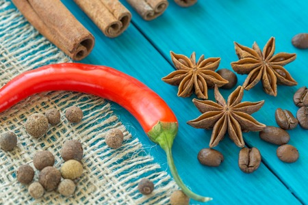 red chili pepper, coffee beans, cinnamon sticks and star anise on wooden table.