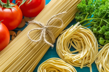 mee: spaghetti and tagliatelle with ingredients for cooking pasta. Curly parsley, garlic, tomatoes. top view. Stock Photo