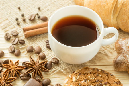 traditional: Black coffee with a oatmeal cookies, cinnamon sticks and star anise on wooden table