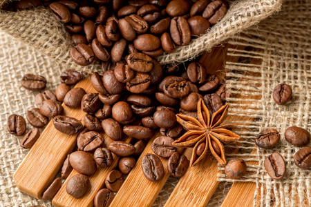 raw: coffee beans in a burlap bag on a wooden background Stock Photo