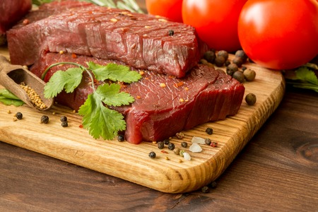 uncooked: raw beef steak with ingredients for cooking on wooden Boards