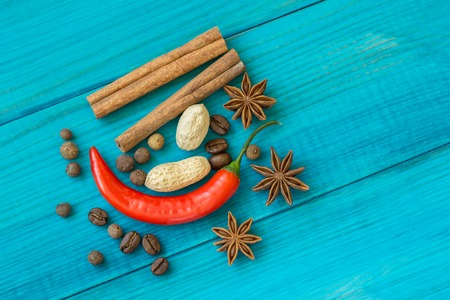 brown: red chili pepper, coffee beans, cinnamon sticks and star anise on wooden table.