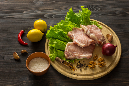cutlets: Slices of raw meat. Pork escalope on a wooden board. With the ingredients for cooking.