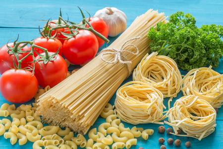 spaghetti and tagliatelle with ingredients for cooking pasta. Curly parsley, garlic, tomatoes on a blue background