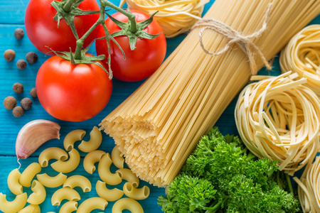 mee: spaghetti and tagliatelle with ingredients for cooking pasta. Curly parsley, garlic, tomatoes on a blue background