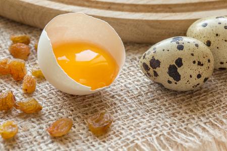 quail: Ingredientes para cocinar. Yema en el caparazón de un huevo de gallina y unos pocos huevos de codorniz.