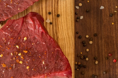 dark: raw beef steak with ingredients for cooking on wooden Boards