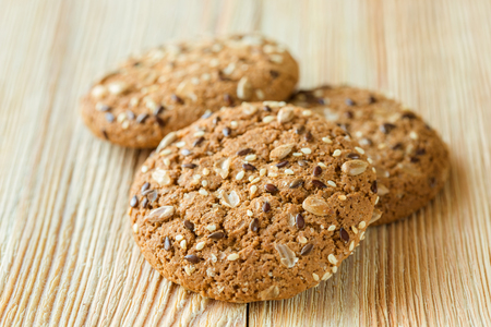 Few oatmeal cookies with seeds on a wooden table. Stock Photo