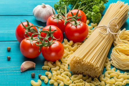 carbohydrates: spaghetti and tagliatelle with ingredients for cooking pasta. Curly parsley, garlic, tomatoes on a blue background