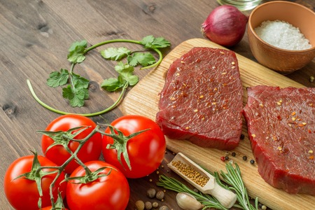 spice: raw beef steak with ingredients for cooking on wooden Boards