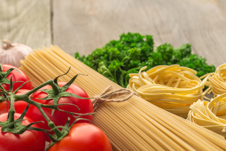 europe: spaghetti and tagliatelle with ingredients for cooking pasta. Curly parsley, garlic, tomatoes on a wooden table.