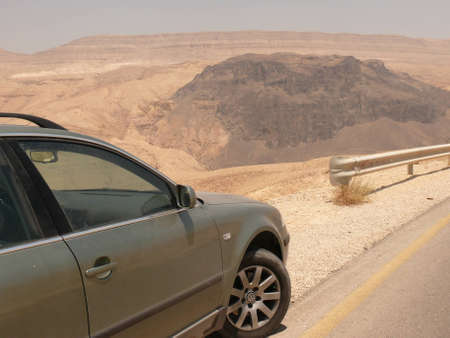 Dusty car on asphalt road, desert highway, with rocks in the background, rocky desert, Kings highway, Jordan, Middle East photo