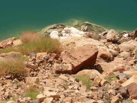 mineralized: Stony shore of the Dead Sea, pebbles, emerald water surface and salt sediments Stock Photo